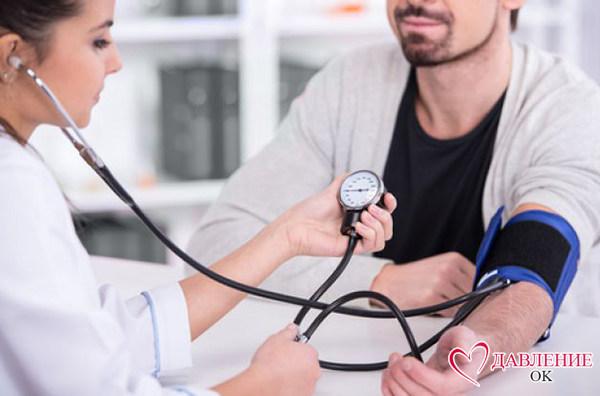 врач замеряет давление у парня